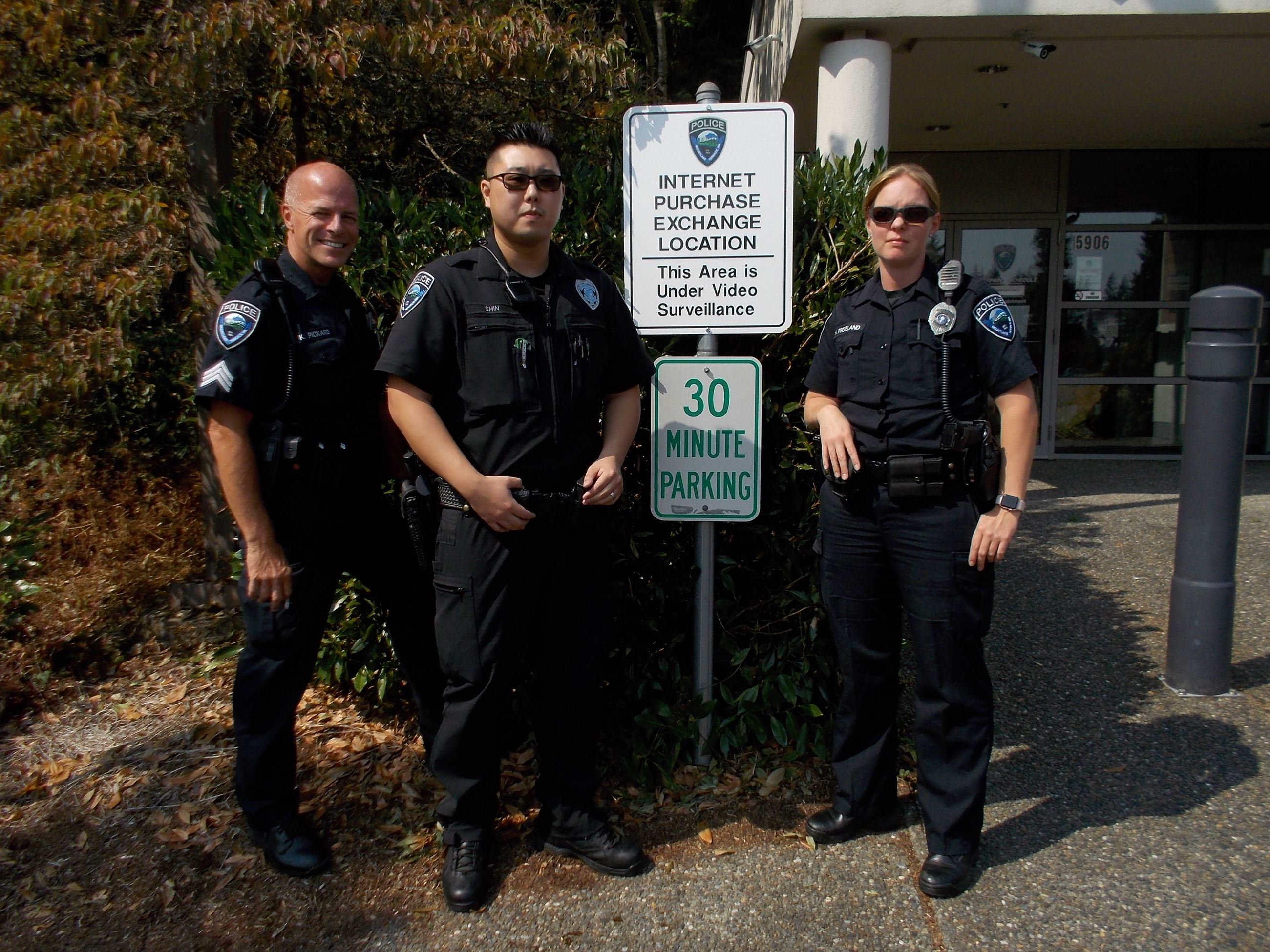 Three officers standing at Safe Internet Transaction Location sign