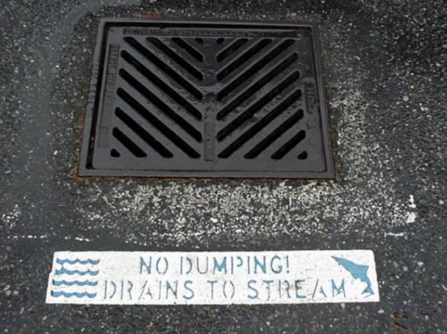 No Dumping sign on storm water runoff grate.