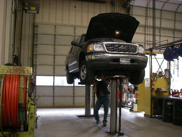 Mechanic Shop with dark car up on the lift.